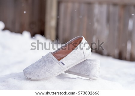 BEND, OR - JANUARY 21, 2017: White Toms shoes outdoors in the snow before a wedding ceremony in which the bride will wear these flats.