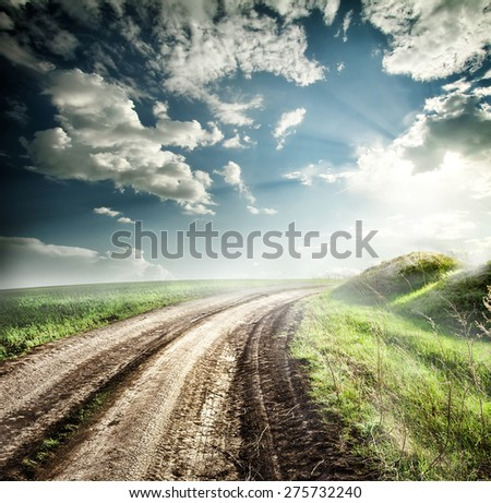 Bend the road in fog of hills under dramatic sky - stock photo