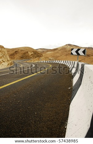 Bending road in the Israeli desert on the way to dead sea - stock photo