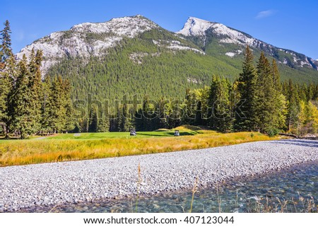 Beneaped autumn stream with a pebbly bottom flows among the mountains. Magnificent picturesque valley in Banff National Park - stock photo