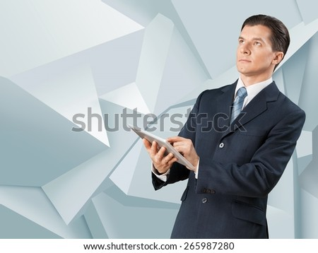 Benefit. Image of businessman holding ipad in hands - stock photo