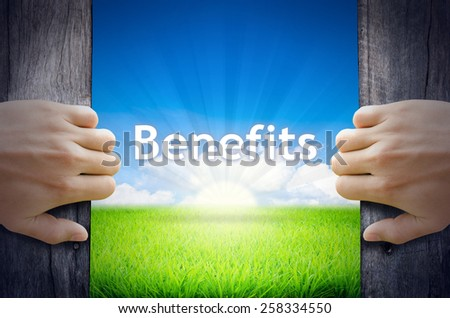 Benefits. Hand opening an old wooden door and found Benefits word floating over green field and bright blue Sky Sunrise. - stock photo