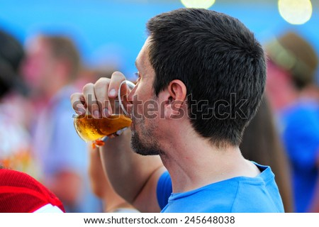 BENICASSIM, SPAIN - JULY 19: A man from the crowd drinks a glass of beer at FIB (Festival Internacional de Benicassim) 2013 Festival on July 19, 2013 in Benicassim, Spain. - stock photo