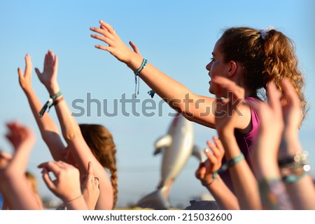 BENICASSIM, SPAIN - JULY 20: Young woman from the crowd cheering at FIB Festival on July 20, 2014 in Benicassim, Spain. - stock photo