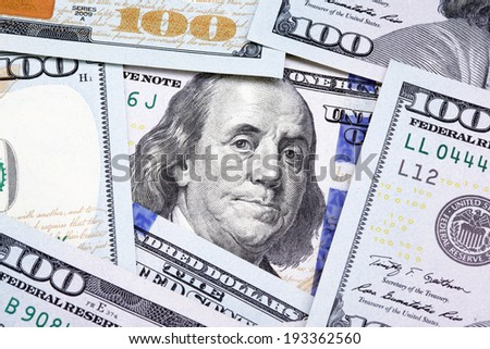 Benjamin Franklin on the one hundred dollar bill framed by other banknotes