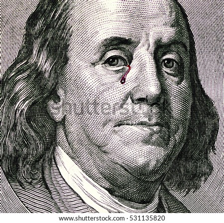 Benjamin Franklin portrait on one hundred dollar bill. Franklin portrait with tears of blood. Franklin crying. Dollars close up.