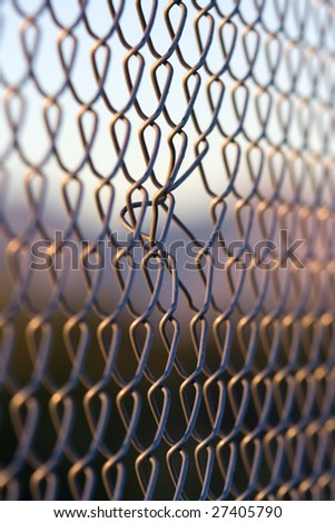 Bent chain links in fence taken at sunset - stock photo