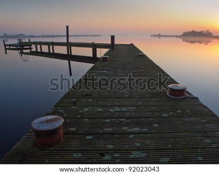 Bent jetty with mooring post during sunset over lake - stock photo