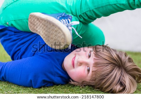 Bent young caucasian girl lying on grass on her back - stock photo