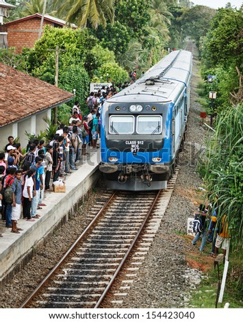 BENTOTA, SRI LANKA - APR 28: Train arrive to station with people on Apr 28, 2013 in Bentota, Sri Lanka. Trains are becoming more popular transport due to railway improvement by government.  - stock photo