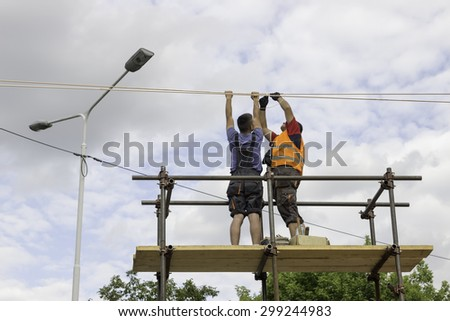 BEOGRAD, SERBIA - JULY 16, 2015:  Workers installing the tram supply power system. Overhead line electrification for new tram system. Selective focus and shallow dof.