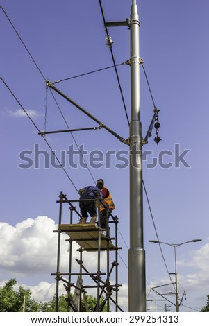 BEOGRAD, SERBIA - JULY 14, 2015:  Workers installing the tram supply power system. Overhead line electrification for new tram system. Electrification for tramways. Selective focus and shallow dof.