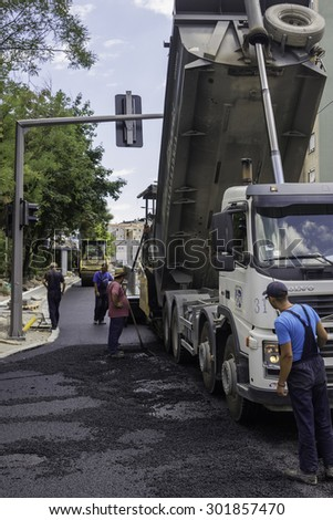 BEOGRAD, SERBIA - JUNE 21, 2015: Asphalt paving workers during road renewal works. Selective focus and shallow dof.