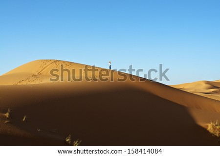 Berber bedouin on sand dune in the desert with traditional clothing - stock photo
