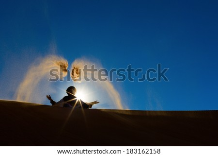 Berber playing and throwing with sands in Desert Sahara, creating angel with sands, Morocco - stock photo