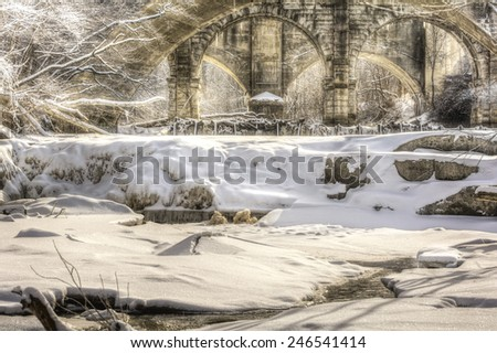 Berea Falls Ohio during winter. This cascading waterfall is in Berea Ohio . The stone arch train bridges make for a nice background in the snowy winter scene. - stock photo