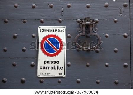 BERGAMO, ITALY - NOVEMBER 4, 2015: Old metal doorknocker and the No Parking sign on the black painted wooden gate fixed with rivets in Bergamo, Lombardy, Italy. - stock photo