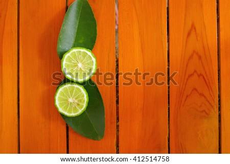 Bergamot cut half with leaves on wood background - stock photo