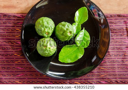 Bergamots with their leaves in black plate on the table that laid by Thai's texture cloth - stock photo