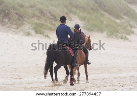BERGEN AAN ZEE, NETHERLANDS - SEPTEMBER 11, 2005: Father and daughter riding horses on the beach. This beach is well known for the large dunes running parallel to the shoreline.