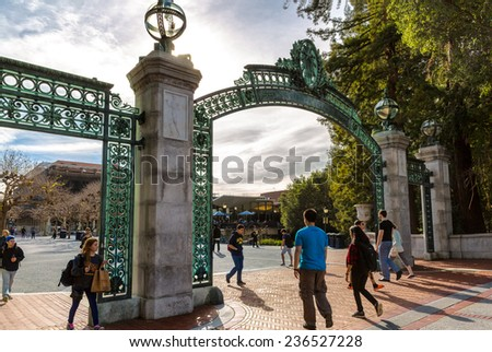 BERKELEY, CA-DEC 8, 2014: University of California at Berkeley at the main entrance into the campus. Students are shown walking under the historical landmark, called Sather Gate. - stock photo