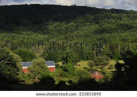 Berkshires, MA, USA - July. 25. 2010: Traditional red barn in the farmland, Berkshires, state of Massachusetts, USA - stock photo