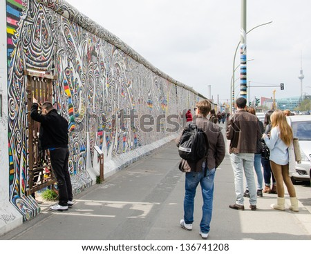 BERLIN, APRIL 24: Graffiti at the East Side Gallery on April 24, 2013 in Berlin, Germany. The East Side Gallery is the longest preserved stretch of the Berlin wall. Some parts are being removed now. - stock photo