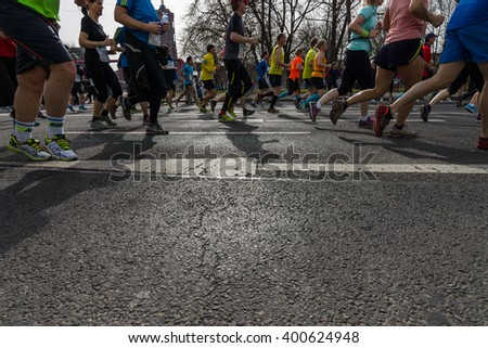 BERLIN - APRIL 03, 2016: The annual Berlin Half Marathon. Race through the city streets. Legs of athletes close-up. - stock photo