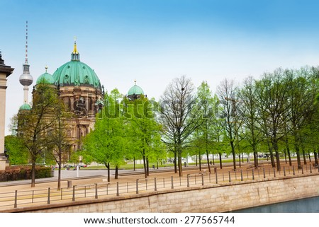Berlin Cathedral Church and Berliner Fernsehturm near embankment with trees in Berlin, Germany - stock photo
