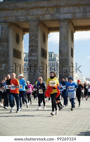 BERLIN, GERMANY - APRIL 1: A group of runner pass under the Brandenburg Gate during the 32nd Vatenfall Berlin half marathonon on April 1, 2012 in Berlin, Germany. - stock photo