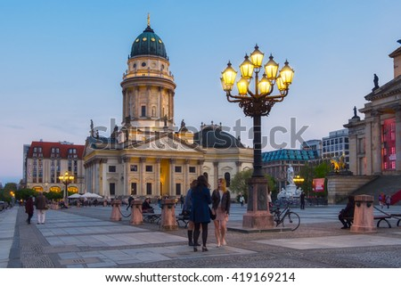 BERLIN, GERMANY - APRIL 30, 2016: French Cathedral on Gendarmenmarkt in evening light. Both visitors and berlin inhabitans enjoy warm Spring evening. - stock photo