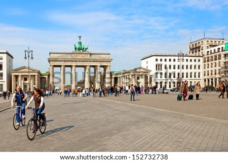 BERLIN, GERMANY - APRIL 2013: People moving in the scenic Pariser Platz, where Brandenburg Gate is located, the most emblematic landmark of the city on April 20, 2012 in Berlin. - stock photo