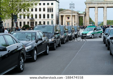 BERLIN, GERMANY - APRIL 11, 2014: Police guarding the convoy of cars with very important people near the Brandenburg Gate. - stock photo