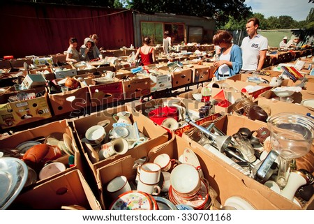 BERLIN, GERMANY - AUG 30, 2015: Vintage cups, plates and people buying it on flea market Mauerpark on August 30, 2015. Urban area of Berlin comprised 4 million people, 7th most populous in EU - stock photo