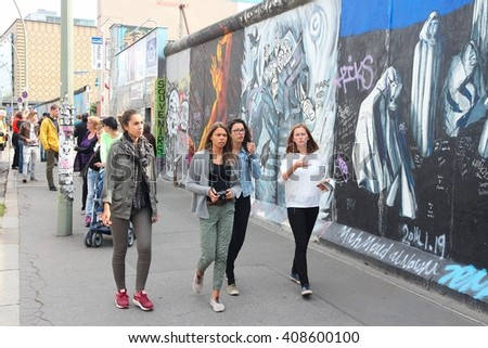 BERLIN, GERMANY - AUGUST 26, 2014: People visit urban art of East Side Gallery at public street in Berlin. Part of former Berlin Wall is covered in art by more than 100 artists since 1990. - stock photo