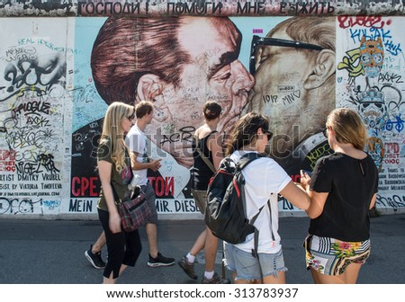 BERLIN, GERMANY - AUGUST 30, 2015: Tourists taking pictures on the famous Berliner Mauer. Graffiti at the East Side Gallery in Berlin, Germany