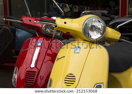 BERLIN, GERMANY - AUGUST 14: Yellow and Red Italian designed Vespa scooters for sale August 14, 2014 in Berlin, Germany - stock photo