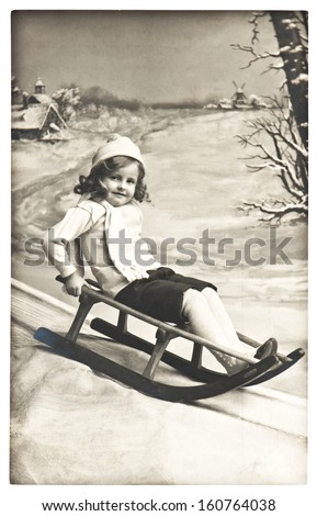 BERLIN, GERMANY - CIRCA 1911: old photo of unidentified little girl with sled in winter outdoors. nostalgic vintage picture from ca. 1911, in Berlin, Germany - stock photo