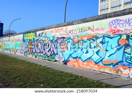 BERLIN, GERMANY - FEBRUARY 26, 2015: The East Side Gallery, one of the last remaining pieces of the original Berlin Wall, stretches for 1.3 km along Muhlenstrasse - stock photo
