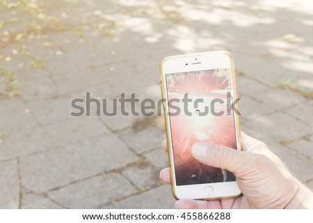 BERLIN, GERMANY - JULY 21, 2016: Catching a Pokemon in the Pokemon Go game app on an iPhone in Berlin, Germany as the augmented reality app was recently released by Nintendo for the German market. - stock photo