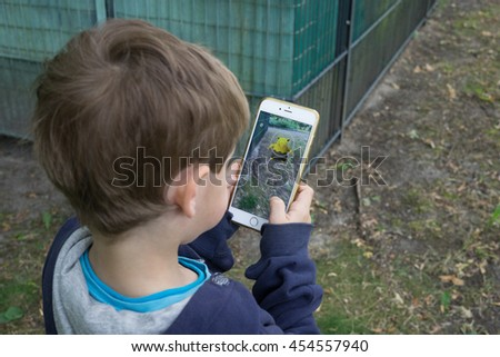 BERLIN, GERMANY - JULY 18, 2016: Five year old boy playing Pokemon Go in Berlin, Germany as the augmented reality app was released by Nintendo for the German market. - stock photo