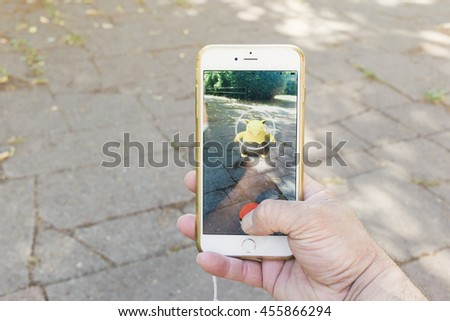 BERLIN, GERMANY - JULY 21, 2016: Pokemon Go, catching a Pokemon in the game app on an iPhone in Berlin, Germany as the augmented reality app was recently released by Nintendo for the German market. - stock photo