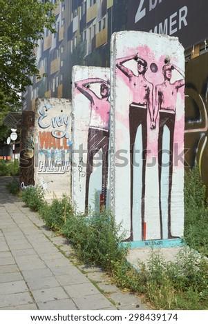 BERLIN, GERMANY - JULY 07: Segments of Berlin Wall in East Berlin filled with grafitti art. July 07, 2015 in Berlin. - stock photo