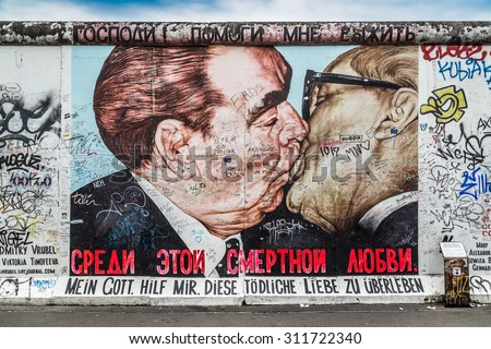BERLIN, GERMANY - JULY 12: Street art graffiti painting 'The Kiss' by Dmitri Vrubel at famous East Side Gallery, the longest preserved section of the Berlin wall, on July 12, 2015 in Berlin, Germany. - stock photo