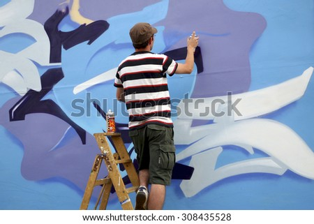 BERLIN, GERMANY, JULY 8: Unidentified painter in action on the wall of Berlin, painting a blue graffiti. Germany 2008 - stock photo