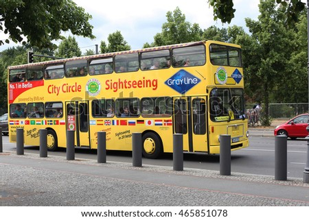 BERLIN, GERMANY - JULY 18, 2016: Yellow City Circle Sightseeing bus tour near The Holocaust Memorial for the Jewish victims of the Holocaust, located one block south of the Brandenburg Gate.