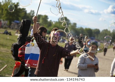 BERLIN, GERMANY - JUNE 10: A young unidentified man making giant soap bubbles on an early summer Sunday afternoon at Mauerpark, and flea market in background, on June 10, 2012 in Berlin,  Germany.