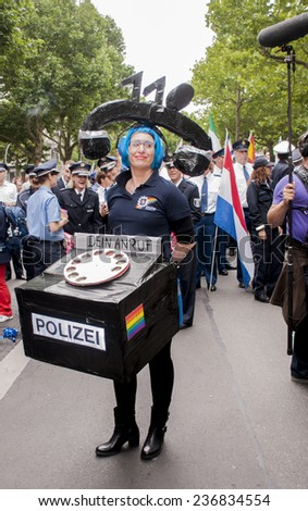 BERLIN, GERMANY - JUNE 21,2014:Christopher Street Day.Crowd of people Participate in the parade celebrates gays, lesbians, and transgenders. Prominent in the image, participant dressed as Police Phone