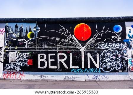 BERLIN, GERMANY - MARCH 20: Berlin Wall graffiti seen on March 22, 2015, Berlin, East Side Gallery. It's a 1.3 km long part of original Berlin Wall which collapsed in 1989. - stock photo