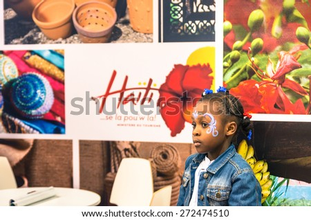 BERLIN, GERMANY - MARCH 8, 2014: female kid at Haiti stand during ITB Travel Trade Show in the fairgrounds of Messe Berlin. Soft focus on the face of the young girl. - stock photo
